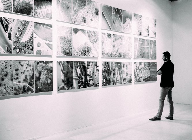 person looking at gallery art pieces in wall photo