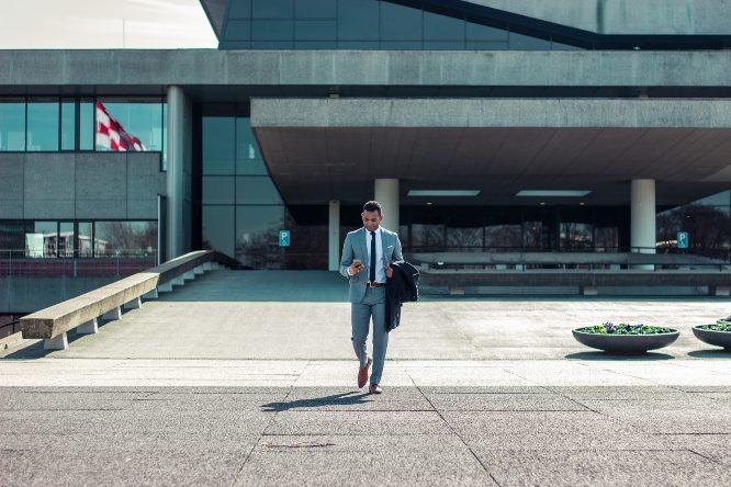 entrepreneur walking while holding black coat