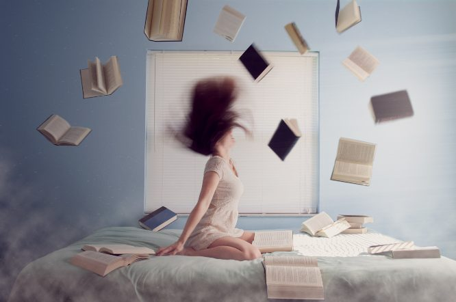 woman sitting on bed with flying books - lacie-slezak-yHG6llFLjS0-unsplash