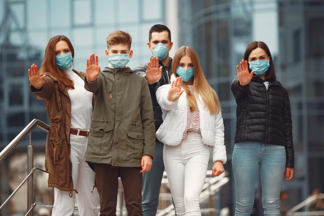 People wearing protective masks are showing stop sign by hands.