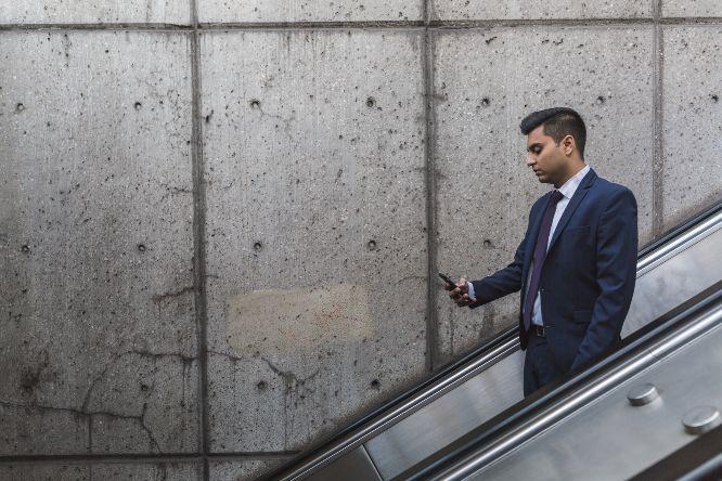negative-space-businessman-mobile-phone-escalator-burst