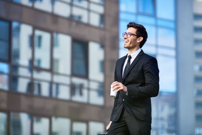 Laughing businessman with drink and briefcase walking down street