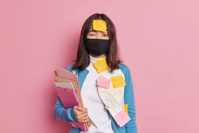prevention-virus-spread-serious-brunette-woman-wears-black-disposable-face-mask-busy-doing-tasks-makes-notes-remember-mathematical-formulas