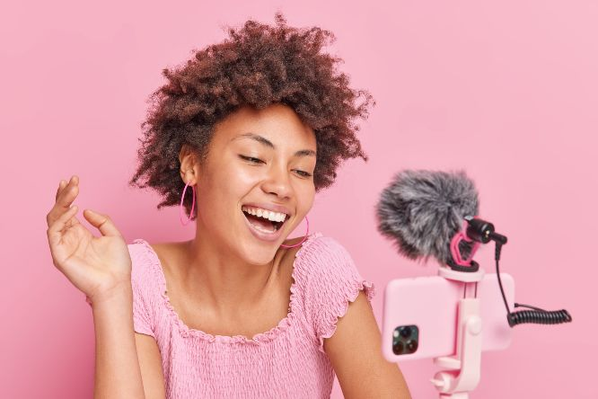 positive-pretty-brunette-afro-american-female-blogger-focused-smartphone-tripod-makes-online-streaming-has-own-channel-smiles-gladfully-poses-against-pink-wall-vlogging-concept